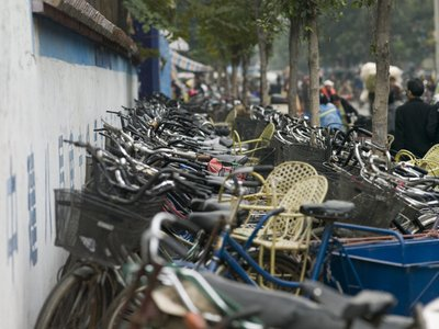 South china, Bicycles parking with people in background Fine Art Print by Assaf Frank