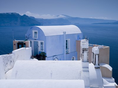 A house pained in ligth blue on the Oia cliff in Santorini Greek Isle. Poster Art Print by Assaf Frank