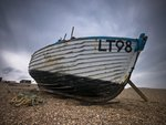 Old fishing boat on pebbled beach Wall Art & Canvas Prints by Assaf Frank