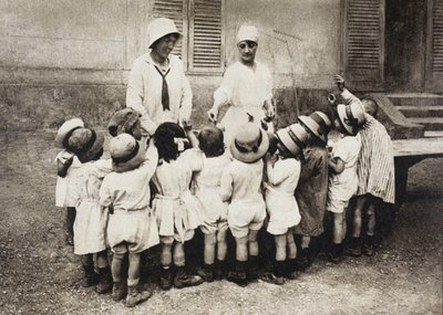 Orphans and refugee children being given pieces of chocolate at the Chateau de Grand-Val in Sucy-en-Brie, France during the First World War, from 'L'Illustration', published in 1918 Fine Art Print by French School