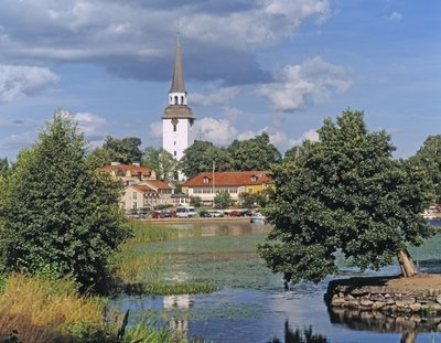 View of the town across the lake Wall Art & Canvas Prints by Anonymous