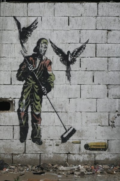 Graffiti depicting a man sweeping bullets, 2010 Fine Art Print by Anonymous