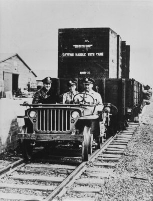U.S. Army jeep fitted with flanged wheels pulling a freight train during the Second World War Fine Art Print by American Photographer