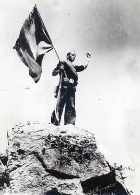 A Republican militiaman raises the army's banner during the advance against rebel troops in the Guadarrama mountains north of Madrid, 1936-39 Fine Art Print by Spanish Photographer