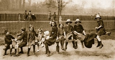 Children play on a see-saw in a London park Poster Art Print by English Photographer