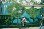 Cyclist speeding past wall painted with comic tableau , Singapore Poster Art Print by P.J. Crook