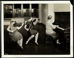 Group of three young blind women, one at the piano, two playing violins, at the New York Association for the Blind, 111 East 59th Street, New York, 1926 Fine Art Print by Byron Company