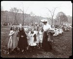 Children in a long line being lead by a woman on Arbor Day at Tompkins Square Park, New York, 1904 Fine Art Print by Byron Company