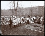 Adults and children holding flags standing around a newly dug hole for a tree planting on Arbor Day at Tompkins Square Park, New York, 1904 Fine Art Print by Byron Company