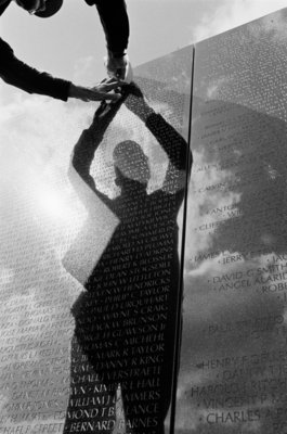 Reflection of a volunteer at the Vietnam Veterans Memorial by Michael Katakis - print