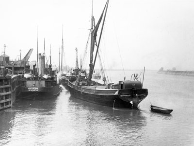The 'Olive May' (1920), a port quarter view of the barge motoring to quayside with her tender in tow (sails furled) by Anonymous - print
