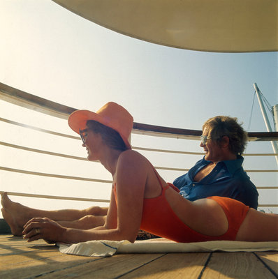 A couple relax and enjoy the sea view on board an unspecificed cruise liner by unknown - print