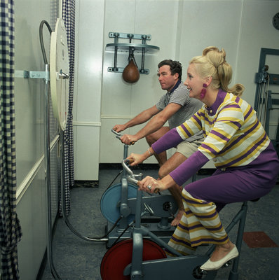 After all the lunches and cocktail evenings, a little exercise is just the thing: two passengers use exercise bikes in the gym of an unspecified cruise liner by Marine Photo Service - print