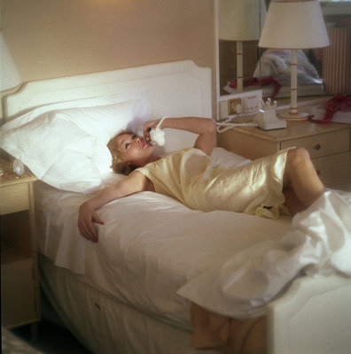 Modern convenience aboard a cruise liner: a female passenger reclines in bed whilst making a phone call; the ship and the conversation's content are unspecified by Marine Photo Service - print