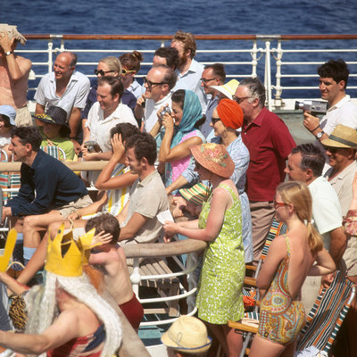 Interested passengers, young and old, enjoy on-deck entertainment aboard an unspecified cruise liner by Marine Photo Service - print