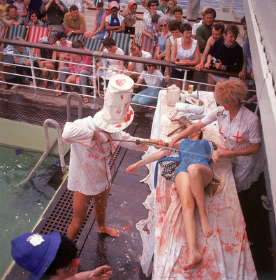 Macabre comic entertainment aboard an unspecified cruise ship, with a female passenger prostrate on a bloody slab - perhaps a variant of the Crossing the Line (the Equator) ceremony? by Marine Photo Service - print