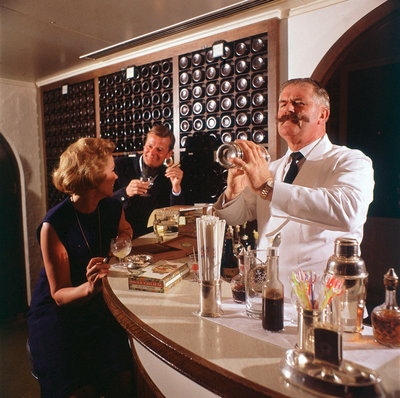 A splendidly moustachioed bartender shakes a cocktail aboard an unspecified cruise liner by Union Castle Line Collection - print