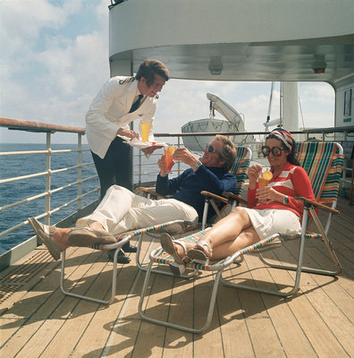 A ship's steward serves drinks to passengers on deck by Marine Photo Service - print