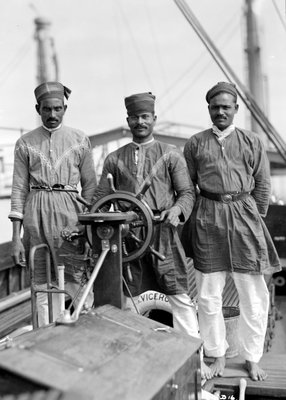 Three Lascars of the 'Viceroy of India' (1929), standing behind the wheel of one of the ship's tenders by Marine Photo Service - print