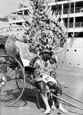 A local rickshaw driver in 'traditional' costume, with a Union-Castle Line ship in the background, at Durban, South Africa by Marine Photo Service - print