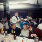 A Victorian themed dinner aboard an unspecified cruise liner, with period costume and fake 'lamb chops' facial hair aplenty, provides much merriment for passengers by Marine Photo Service - print