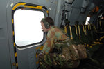 A British Army soldier looks out the window of a RAF Merlin helicopter. Wall Art & Canvas Prints by Ruth Addinall