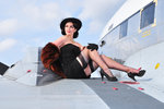 Glamorous woman in 1940's style attire sitting on a vintage aircraft. Wall Art & Canvas Prints by Gustav Klimt