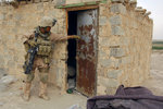 A U.S. Marine searching outside and inside a house during an operation in Tharthar, Iraq. Wall Art & Canvas Prints by Jacob Jordaens